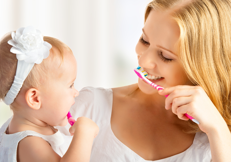 mother and daughter both brushing their teeth