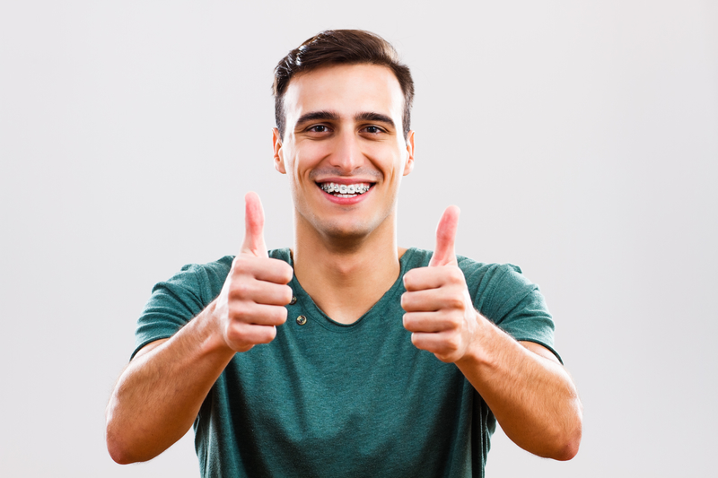 Young adult man that is smiling with braces on his teeth and giving the thumbs up sign.