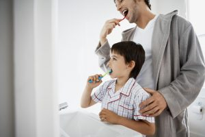 Father and young son brushing teeth together in bathroom