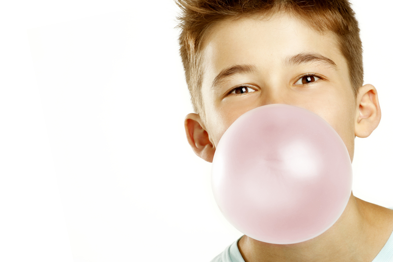 Boy making large bubble gum bubble