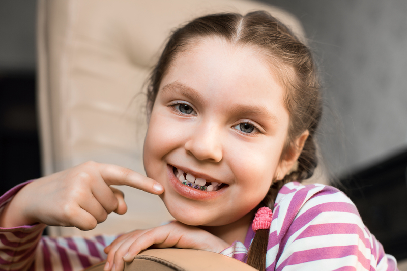 A young girl with braces on her baby teeth that is pointing to her orthodontic metal appliance.