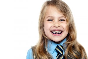A young female patient that is wearing braces and smiling at the camera.