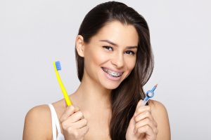 A teen woman with braces on her teeth that is holding a toothbrush in one hand and a braces brush in another hand.