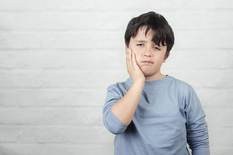 Male child with toothache holding jaw with his hand