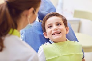 young male child smiling up at dentist in a dental chair