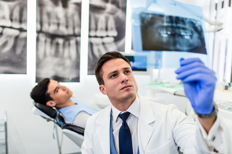 Photo of smiling male dentist looking at patient's x-ray of teeth