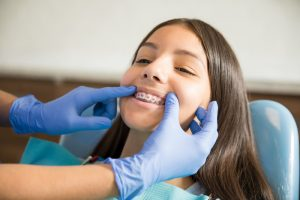 Teenage girl with braces being examined by dentist wearing gloves