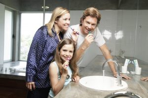 A mother, father and daughter all brushing their teeth in the bathroom together.