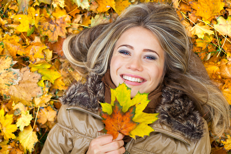 Woman laying in fall leaves and holding one by her mouth. She is smiling at the camera.