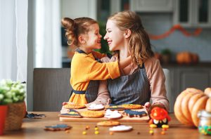 A mother and young daughter smiling as they start to hug. They are sitting in front of Halloween sugar cookies they just finished frosting.