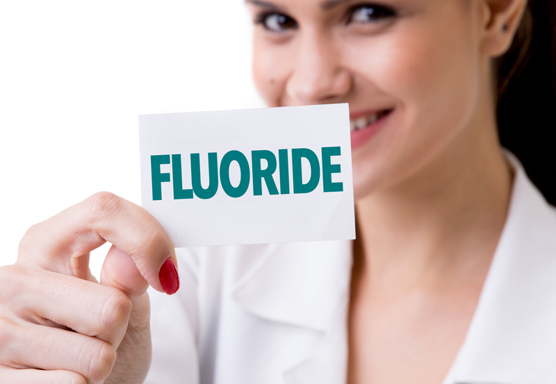 "Woman holding up a sign that says ""fluoride""."