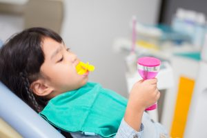 Young boy holding a minute sand timer with a fluoride treatment tray in his mouth at a dental office.
