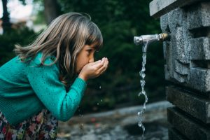 Young girl drinking public water from a spout