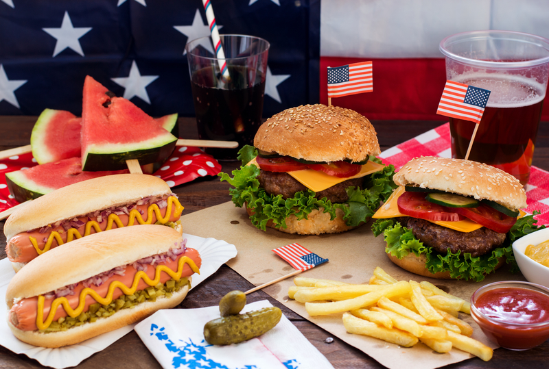 Photo of hamburgers, hotdogs and french fries with an American flag in the background