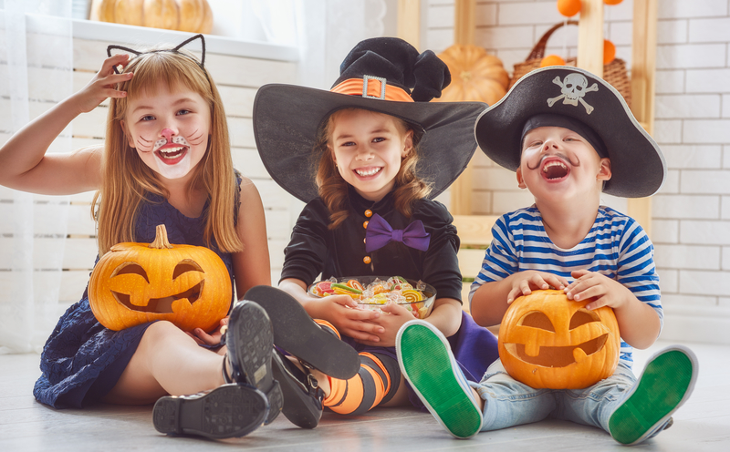 Three kids, one boy and a two girls, sitting together in their Halloween costumes with pumpkin candy baskets.
