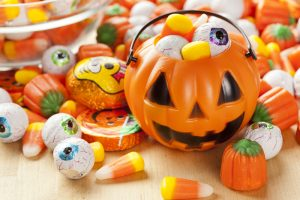 A pumpkin candy basket filled with candy with candy surrounding it.