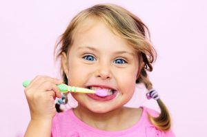 A young female child brushing her teeth with a child toothbrush and smiling towards the camera, in front of a baby pink background.
