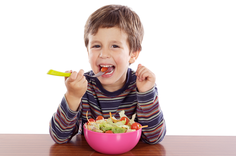 Young boy eating a salad and smiling.