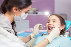Little opening with mouth open as female dentist examines her teeth