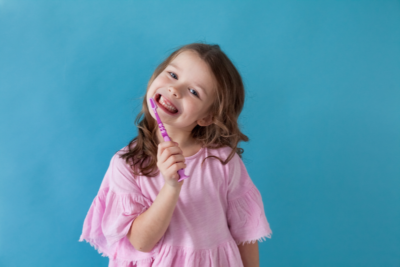 Little girl brushing teeth with toothbrush