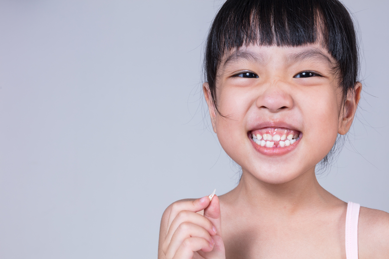 Young Asian girl holding her missing tooth while smiling