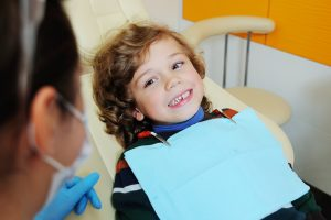 Young toddler boy that is in a dental office for a checkup and is smiling at the dental hygienist.