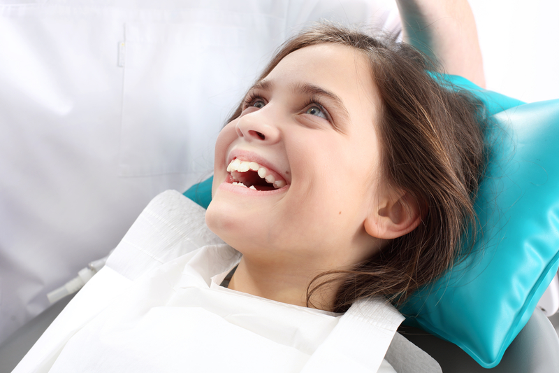 Young girl patient smiling as she is about to have a dental procedure