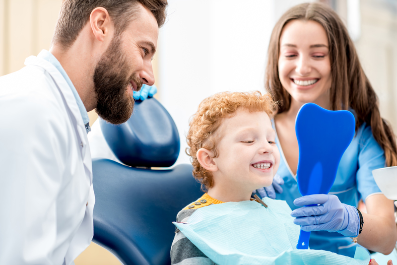 Child looking at teeth in mirror with dentist and assistant