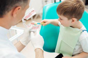 Children brushing practice teeth with dentist