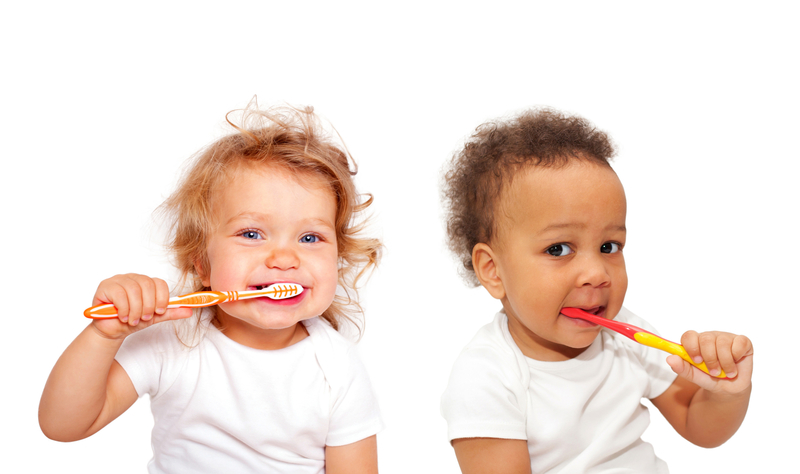 Two babies brushing teeth with toothbrushes
