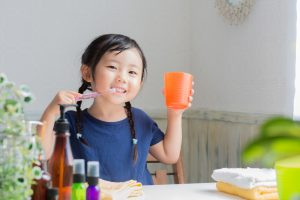 Young asian girl that is brushing her teeth and holding a glass of water.