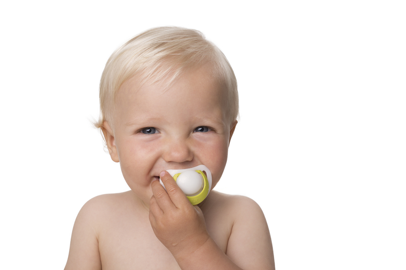 Small male infant smiling and holding a pacifier