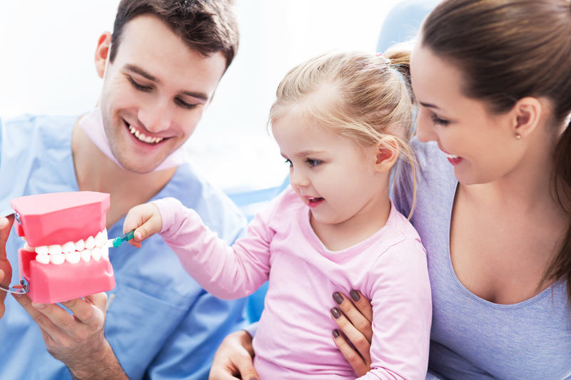 A young man and a young woman holding a small girl and showing her how to brush teeth on a dental model