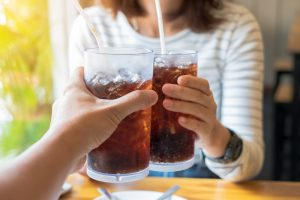 Close-up view of two drinks of soda that some people are drinking.