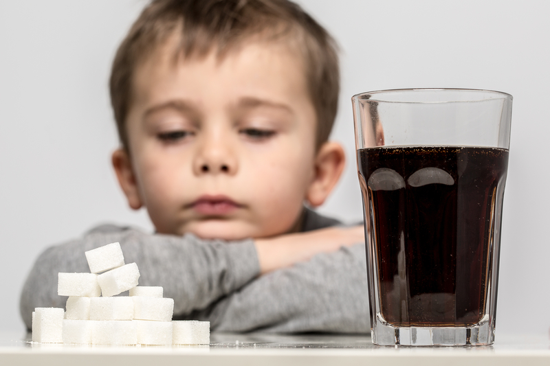 Child sitting in front of sugar cubes and soda