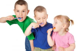 Three children of varying ages that are brushing their teeth