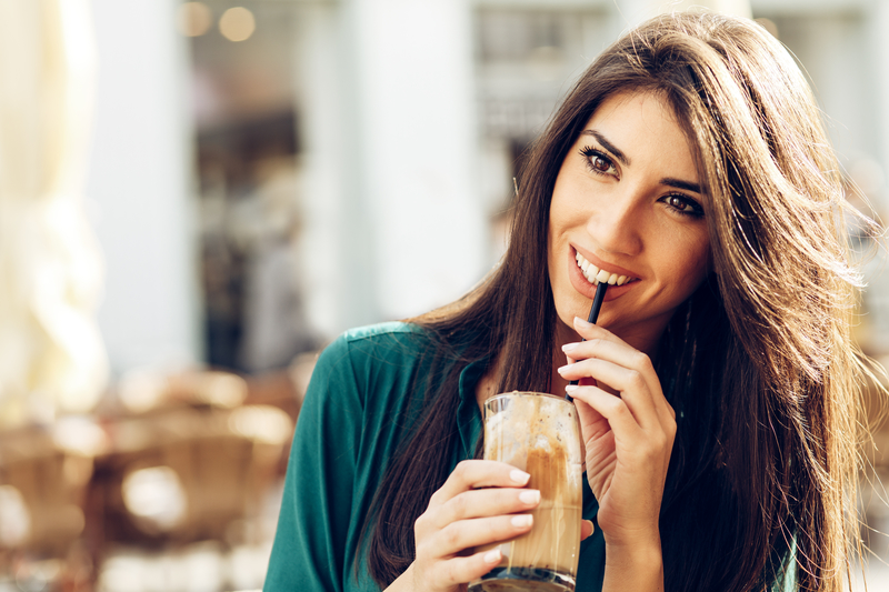 A beautiful brunette young adult woman that is sipping on a coffee drink. She is wearing green.