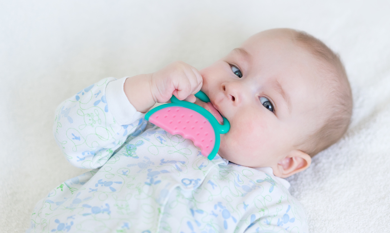 A baby chewing on a teething ring toy.
