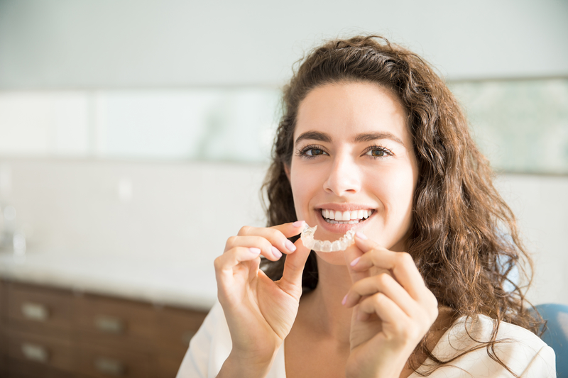 Woman that is smiling as she is going to put a transparent orthodontic aligner in her mouth.
