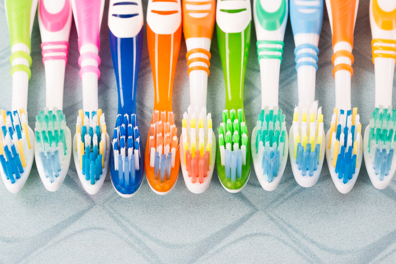 Image of many different colors and sizes of toothbrushes