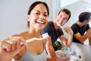 Woman and man brushing their teeth with toothpaste