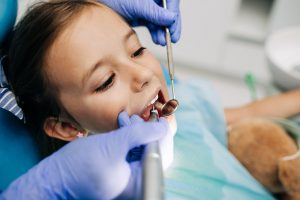Little girl sitting on dental chair and having a dental checkup