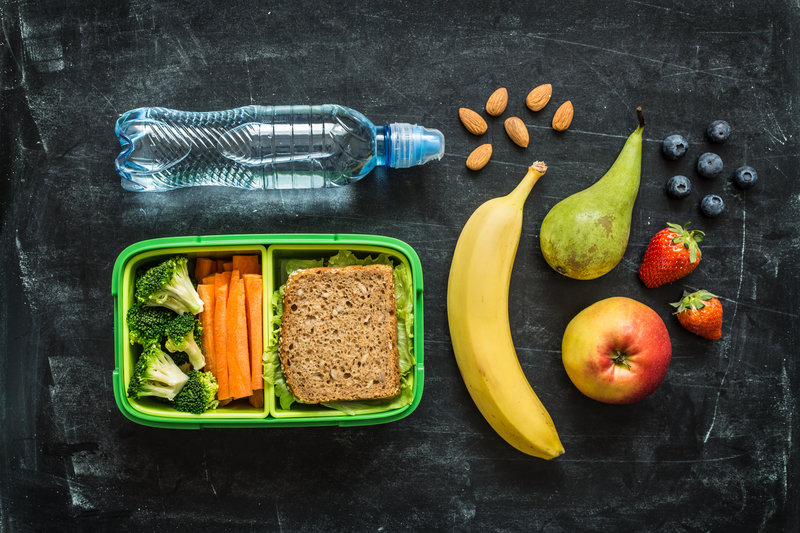 School lunch box with sandwich, vegetables, water, almonds and fruit