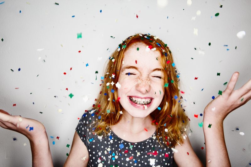 Redheaded teenager throwing confetti in the air while smiling with braces
