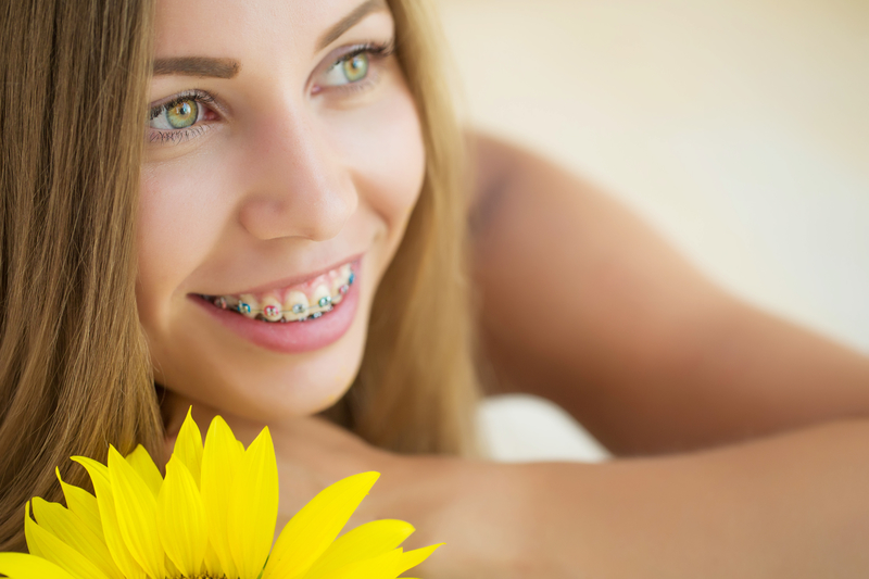 Young female teenager with braces smiling with a yellow flower in the foreground